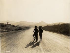 charlie chaplin walks on a road with gamine